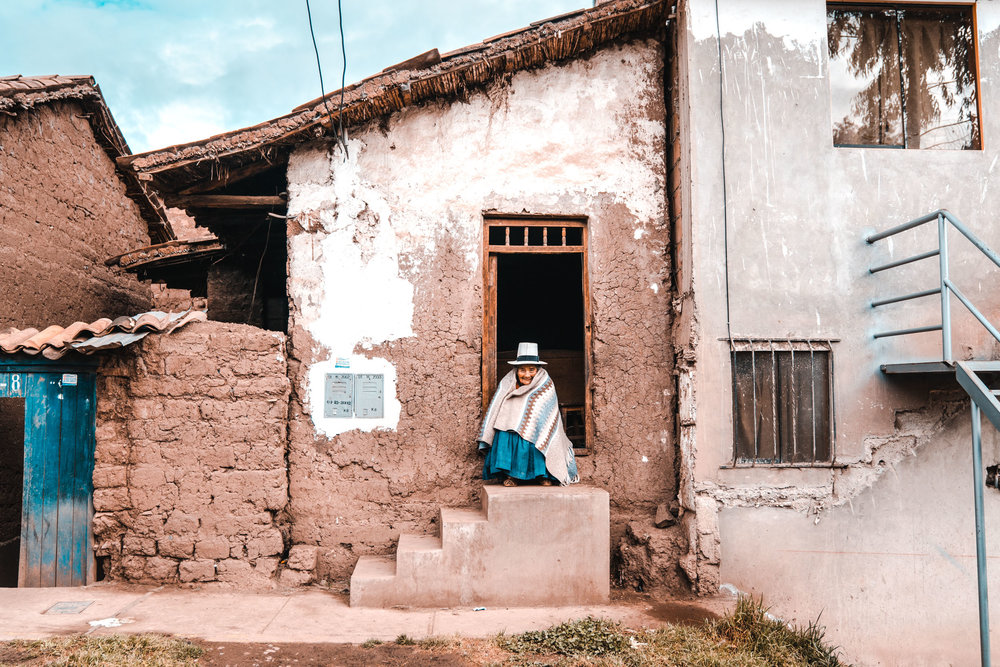 An elderly woman sits outside her house in the early morning. Cusco, Peru 2018