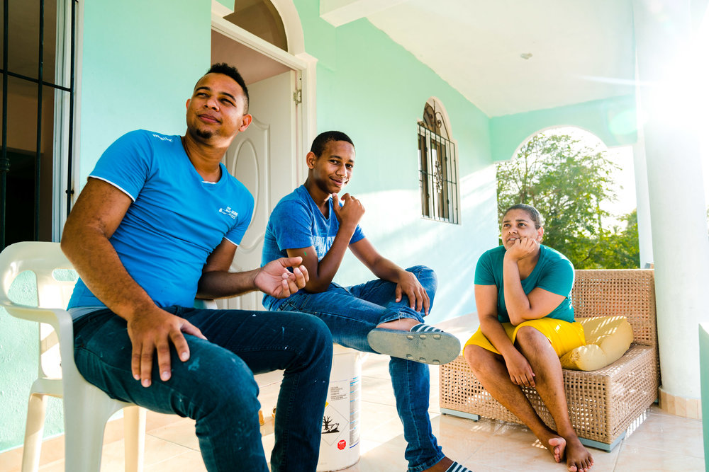 Local Dominican family sit out on their porch in the evening sun. Dominican Republic, 2018