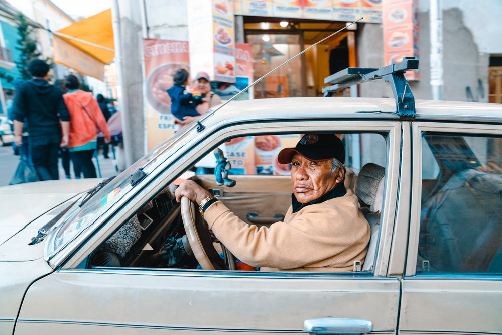 Bolivian man drives past on the busy streets of La Paz. Bolivia, 2018