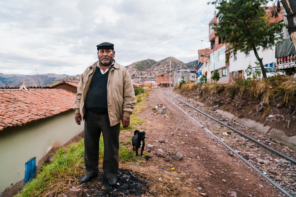 A man stands on side of the winding train tracks just outside Cusco, Peru. 2018