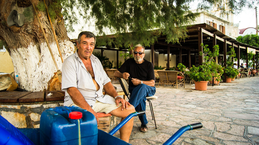 Two local men sit in the early evening under an Olive Tree. Halki, Greece. 2012