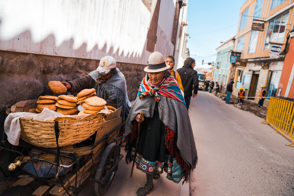 Bolivian woman walks past someone selling traditional break on the street side. Potosi, Bolivia. 2018