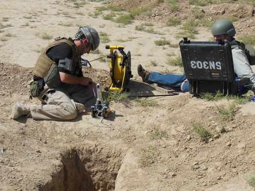 Image: Two team members are setting up a modified pipe inspection robot for a karez inspection test in Afghanistan on Sept. 21, 2012. Courtesy U.S. Army REF.