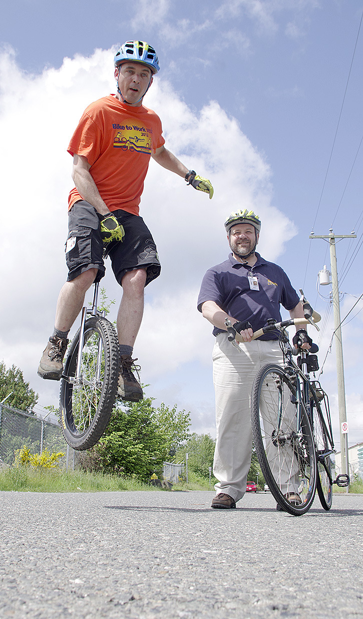 Steve Pilcher, left, tests out the suspension on his unicycle while Craig Senych looks on. Both men are among employees from Inuktun robotics company who will be participating in Bike to Work Week (May 26-June 1