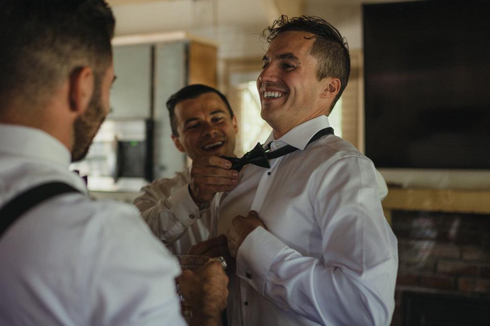 Incline Village wedding groomsmen helping groom get ready photo
