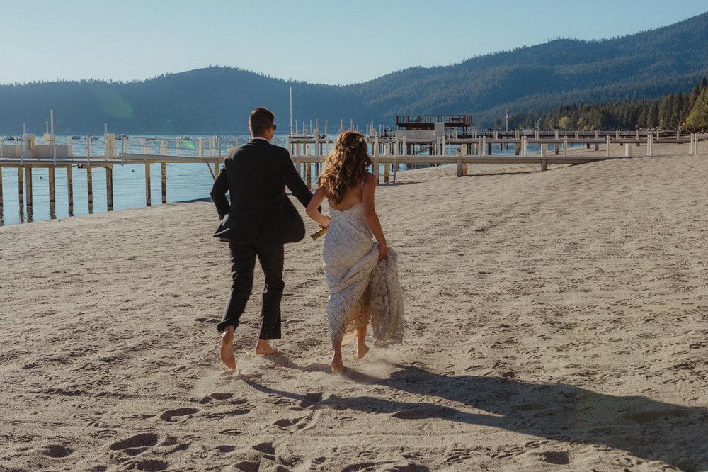 Incline village beach wedding couple running on the sand photo