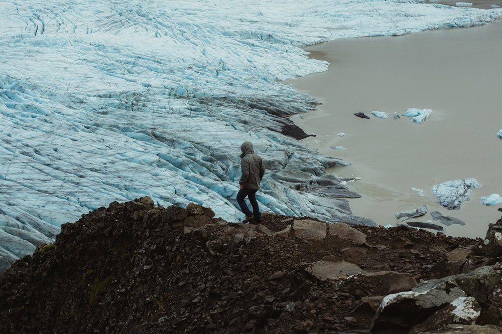 Guy walking by a glacier in Iceland