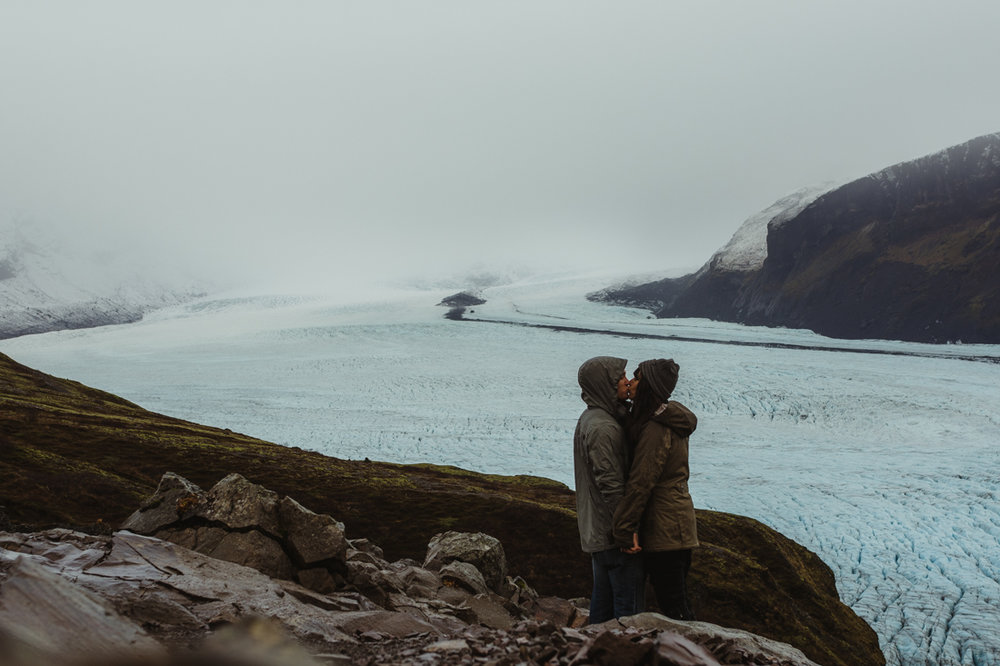 couple kissing next to a glacier in Iceland