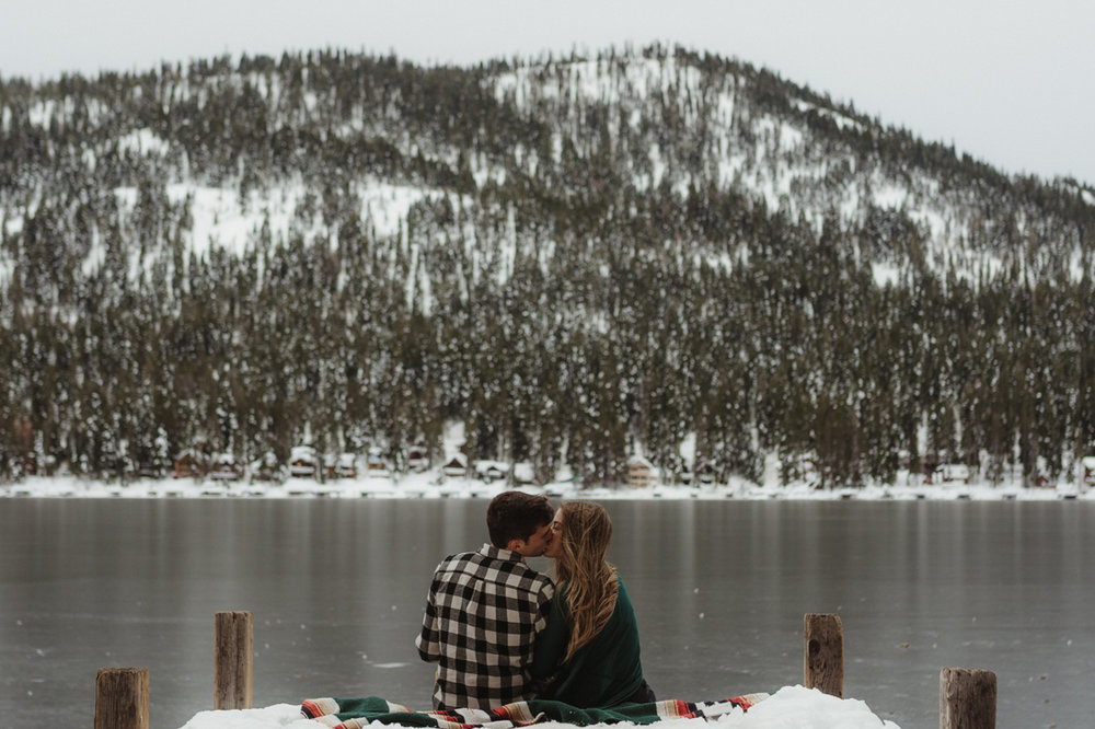 Couple sitting at the edge of a dock in Donner CA photo