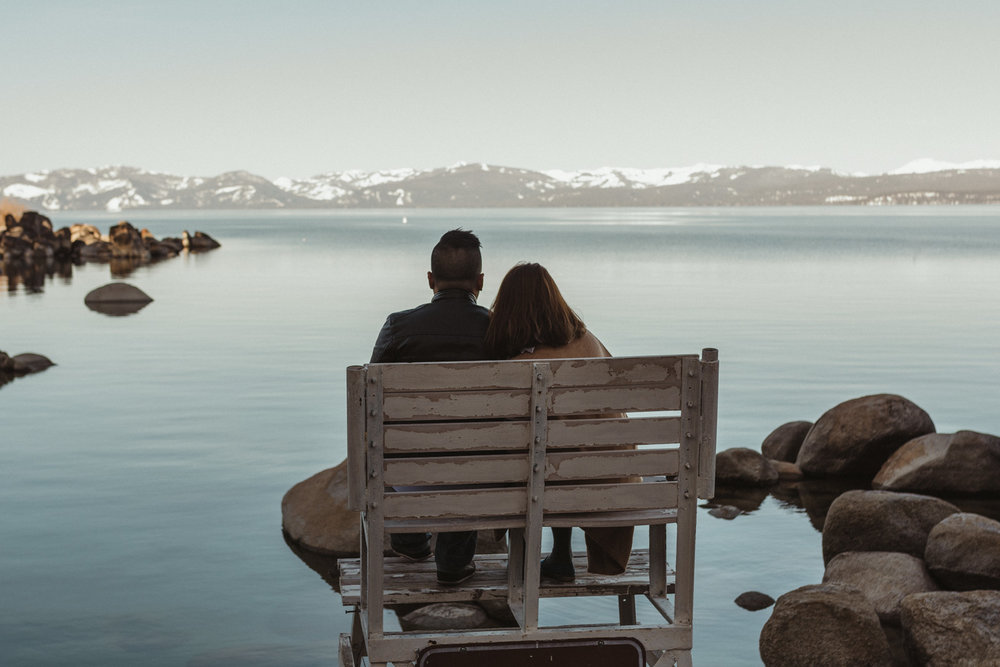 Lake Tahoe engagement session couple sitting down looking at the lake photo