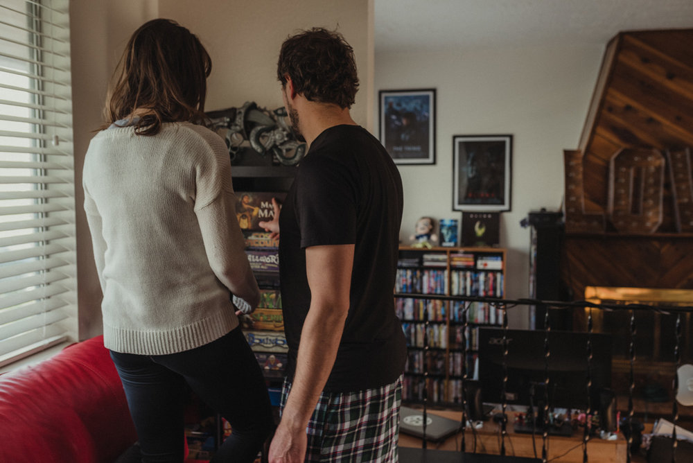 Home session- couple choosing a board game for their engagement photos.