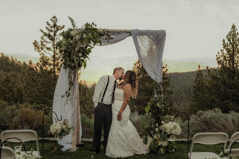 Tannenbaum Wedding couple kissing under a flower arch photo