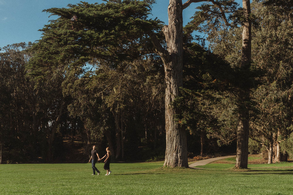 San Francisco engagement photos at Golden Gate Park couple walking by a special tree photo