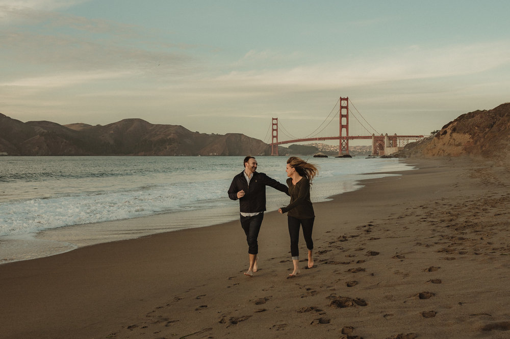 San Francisco engagement couple running at Baker Beach with the Golden Gate in the background photo