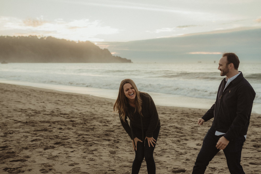 San Francisco engagement couple laughing at Baker Beach photo