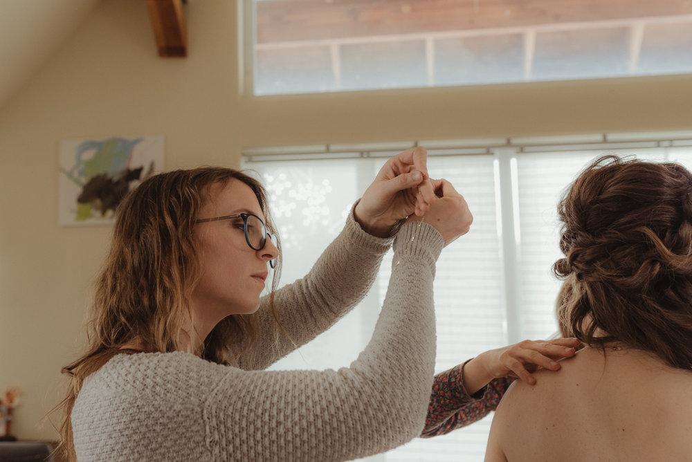 At home Reno wedding bridesmaid helping bride with her necklace