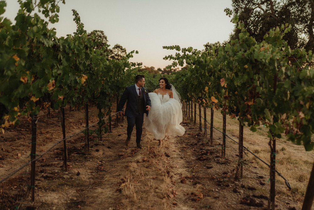 Ranch Victoria vineyard wedding couple running in the vineyard photo