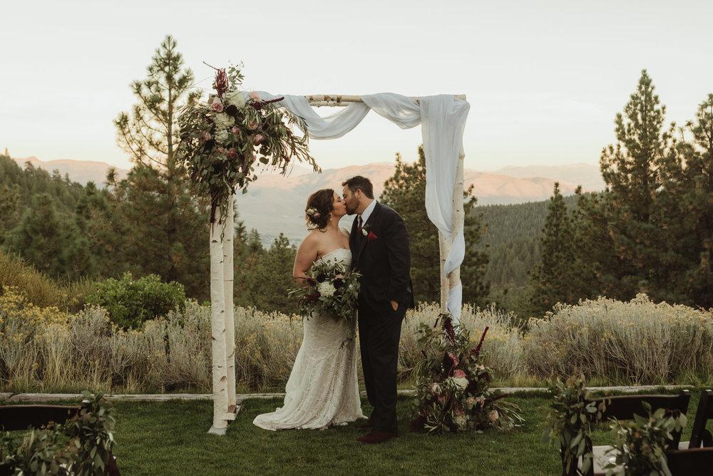 tannenbaum wedding couple under the flower arch photo
