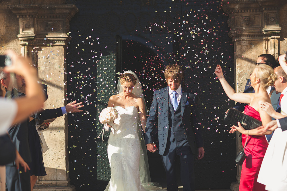 One of a set of images taken at this chic destination Wedding of Jenna & Nick. The stylish old town of Dubrovnik, Croatia.  Confetti is thrown at the beautiful couple.  Photography by Matt Porteous