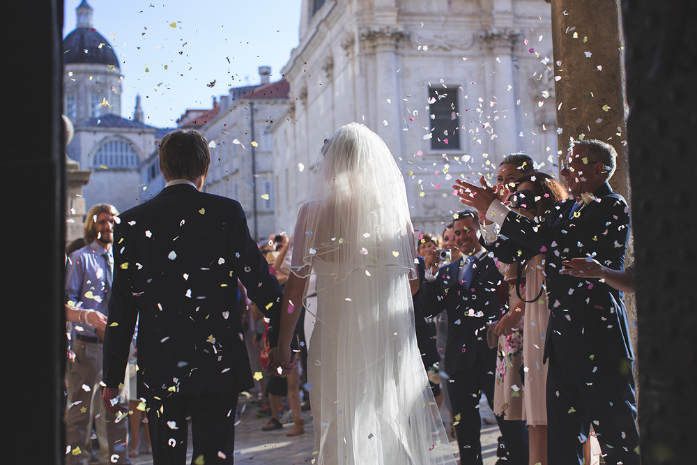 One of a set of images taken at this chic destination Wedding of Jenna & Nick. The stylish old town of Dubrovnik, Croatia.  Confetti is thrown over the couple.  photography by Matt Porteous
