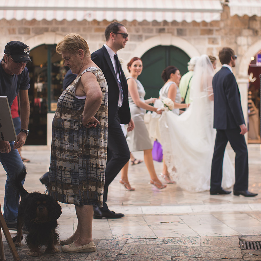 One of a set of images taken at this chic destination Wedding of Jenna & Nick. The stylish old town of Dubrovnik, Croatia.  The bridesmaid lifts the train of the dress.  Photography by Matt Porteous
