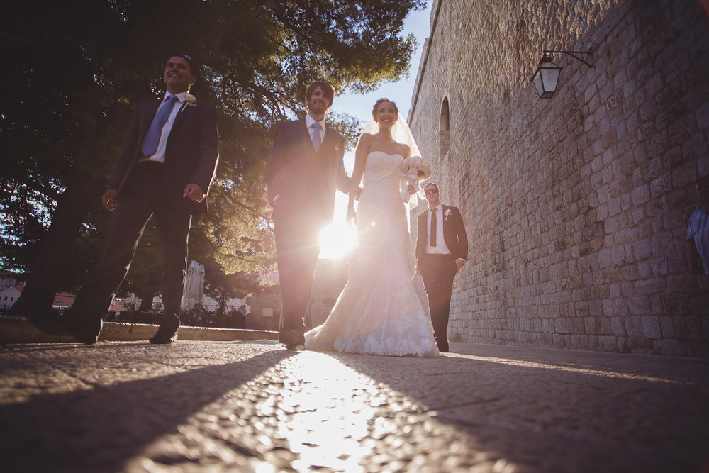 One of a set of images taken at this chic destination Wedding of Jenna & Nick. The stylish old town of Dubrovnik, Croatia.  The couple walk in the sunset.  Photography by Matt Porteous