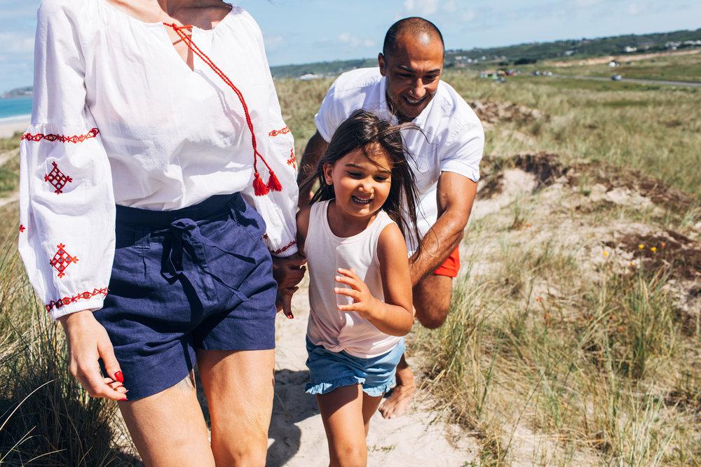 Family running through the beach