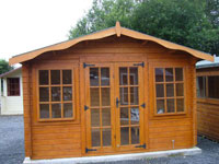 Orange coloured wooden garden shed with glass windows.