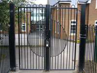 Black security fence and gate in front of a school playground.