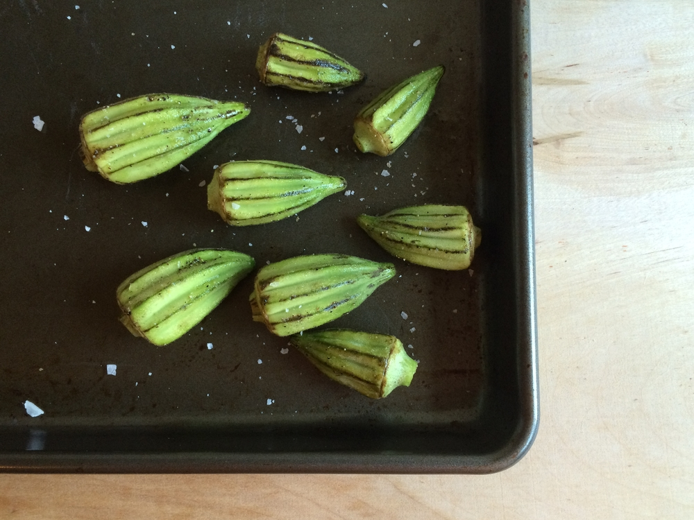 Place whole okra pods in a bowl and toss with olive oil, salt, and pepper.