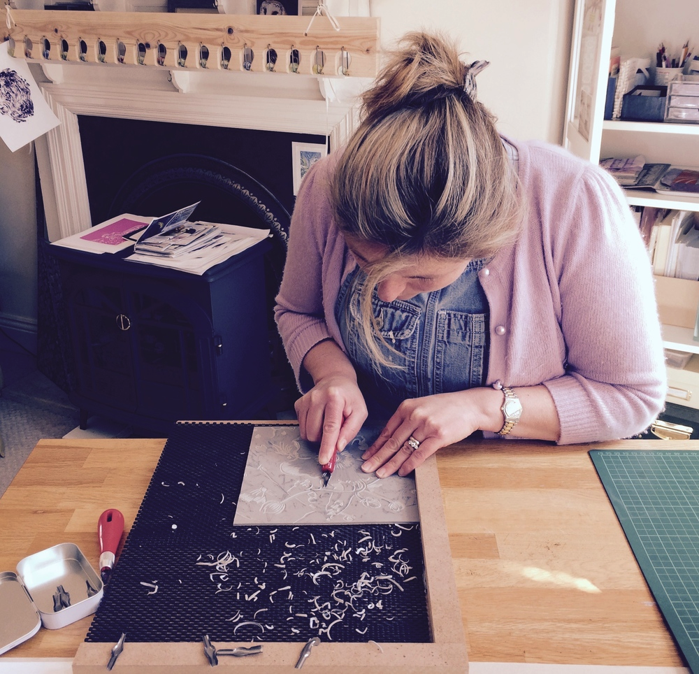 Georgie at her worktable creating linocut artwork.