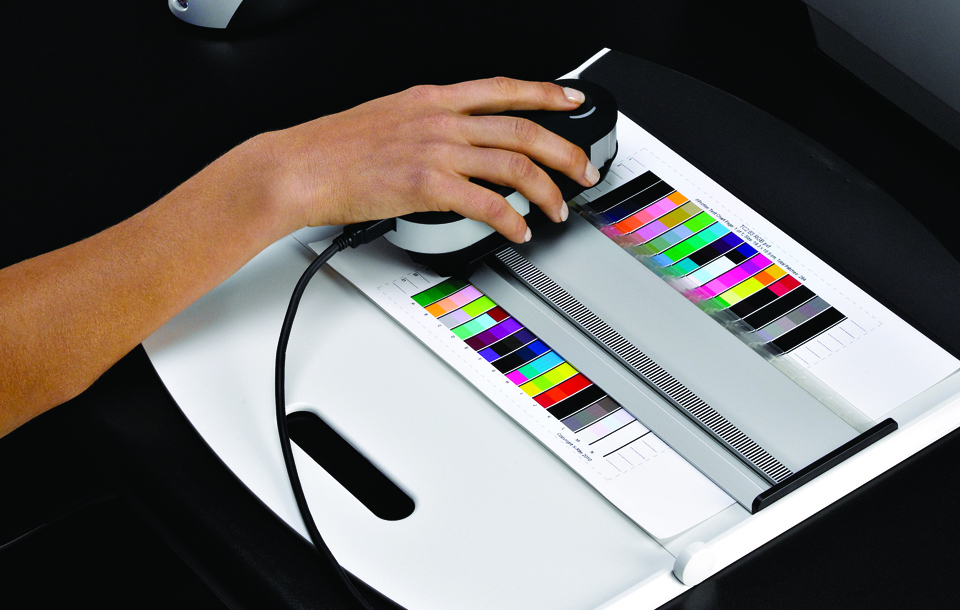Hand measuring a printer profile target with the i1 Pro Spectrophotometer.