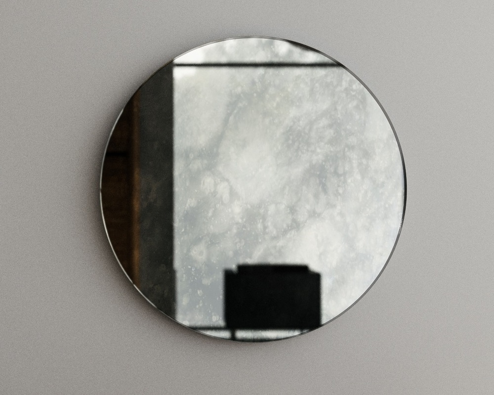 Close up of antiqued round mirror reflecting a Midcentury modern interior.