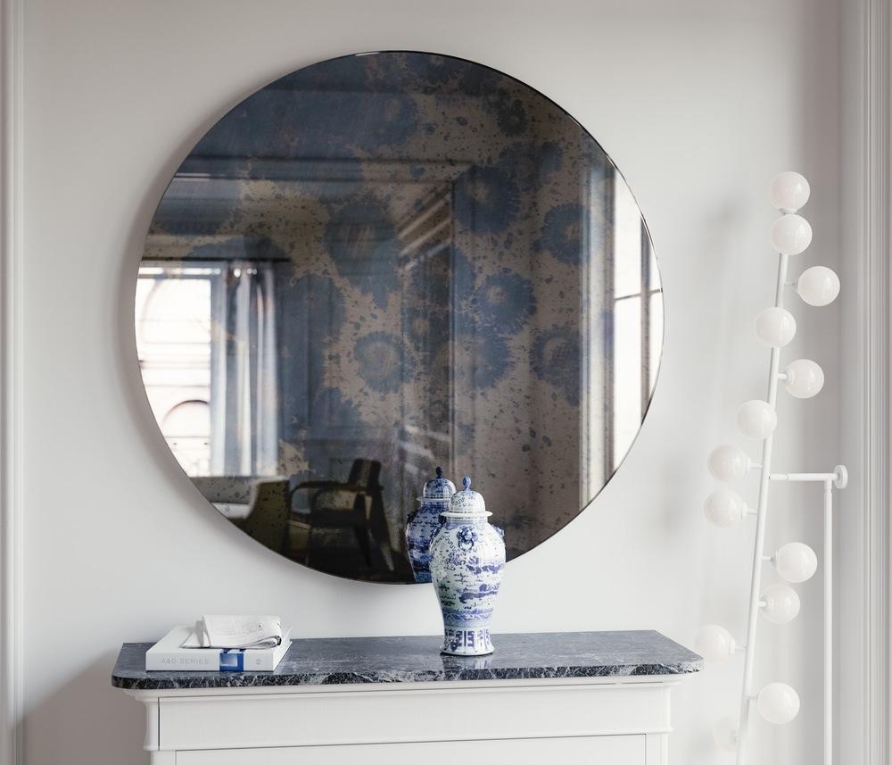 Round, frameless blue antiqued mirror