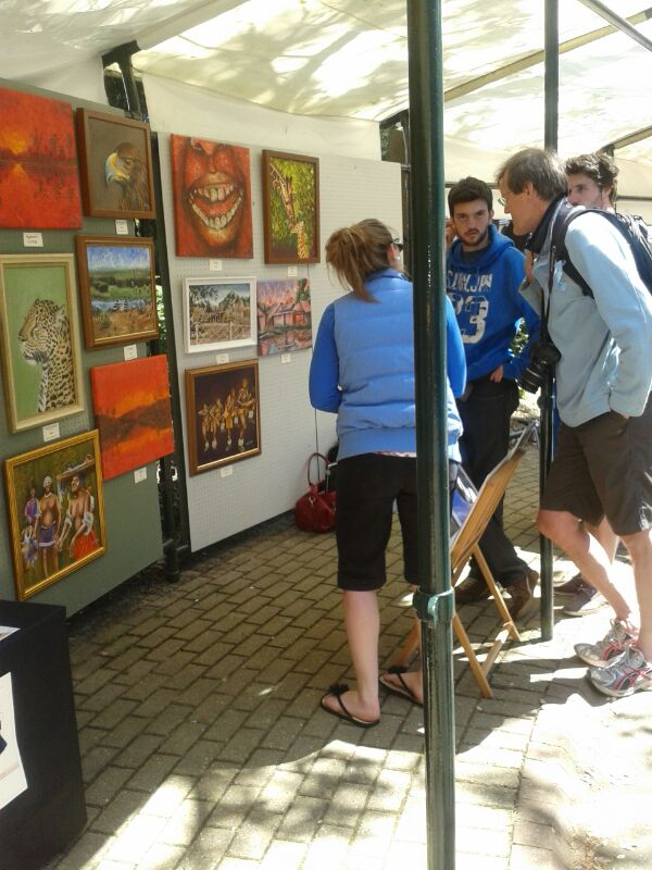 Guests examining Nkolika's art at the Pinewalk Art Exhibition