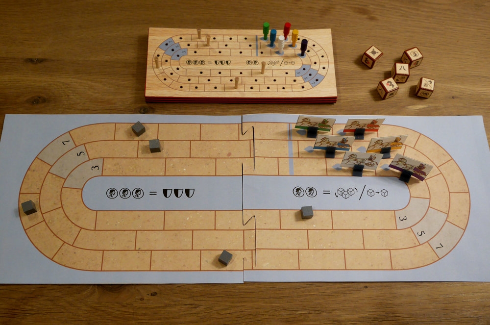 "This is one of the ""wood"" prototypes (made from foam) alongside the board game version. Moving to more traditional materials cut the game's cost by more than half and opened up the possibility of including a double-sided board and variable chariots. The wood was fun but terribly expensive and the chariots (as cribbage pegs) weren't very thematic."