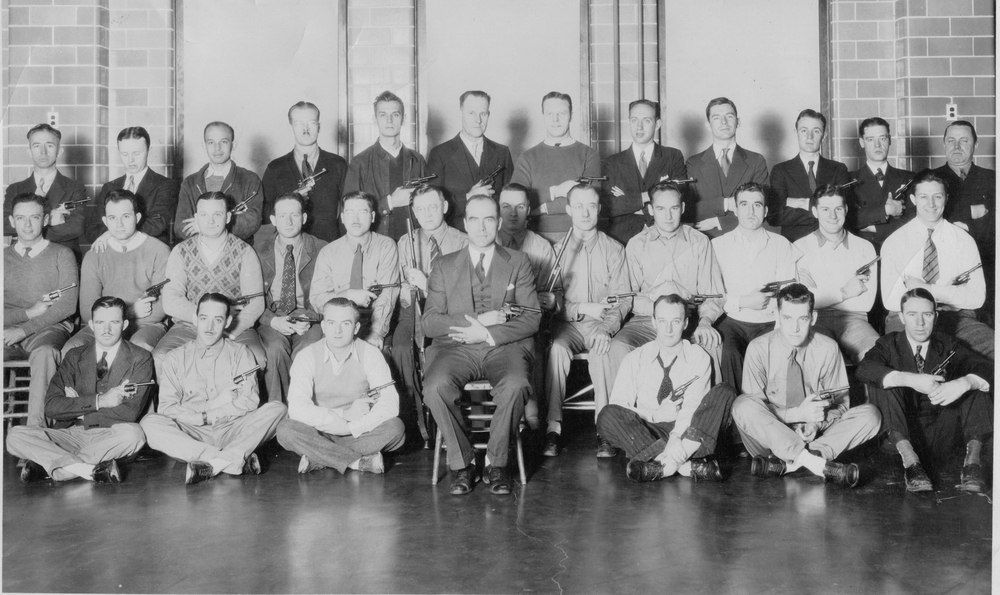 1934 Training Class Of SA Milord Kirkland, Thomas M. McDade & Others       Kirkland (see his bio) is behind the left shoulder of the Agent in the chair, dressed in the suit. Kirkland is holding a rifle. Upon enlarging the photo, we now know that the Agent who is sitting on the floor, 3rd from the right, wearing a black tie pulled down is G. Christopher Callan whose son is currently a retired Special Agent. 2nd from the right, next to Callan, is Agent Myron Gurnea. Sitting in the first row, far left, is SA Thomas M. McDade. We do not know the identity as of yet of the others. (photo courtesy of Kirkland's daughters)