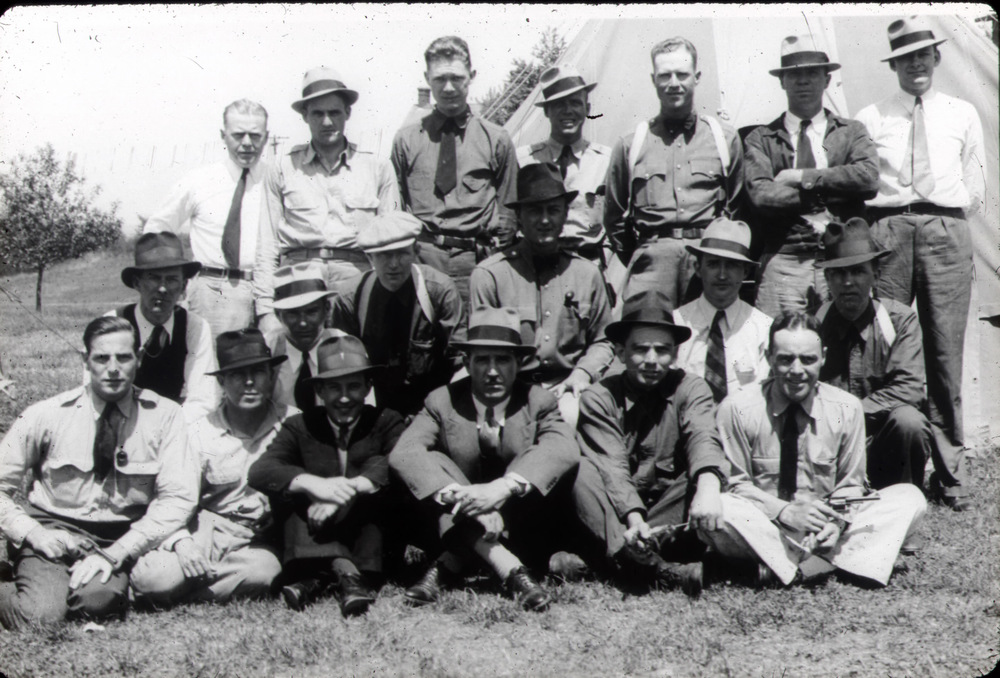 "1935 Training Class Photo Of SA Henry ""Hank"" Sloan And Others    SA ""Hank"" Sloan is shown in back row standing, 5th from the left. The back of this photo, courtesy the Sloan family, reveals ONLY the LAST NAMEs of others as indicated by Sloan's writing. ""Back row - left to right"" - Taylor, Boone, Johnson, Collier, Sloan, Sanders, Sears. ""Middle Row"" l to r: O'Donnell, Mehler, Dierst, Miller, Vincent, Murphy. ""Sitting"" l to r: Connell, Thompson, Conroy, Baughman - Instructor, Mertz, and Coulter"