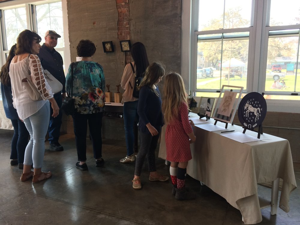 Guests looking at pieces in the show and silent auction
