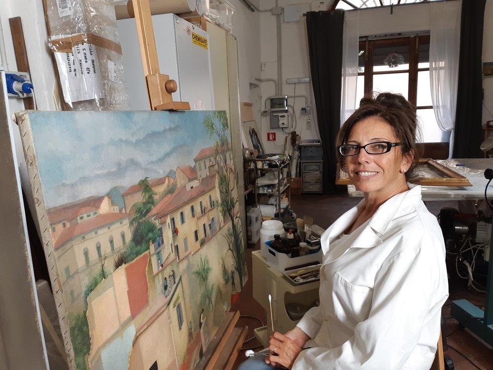 La restauratrice Sandra Pucci con il dipinto della Levasti