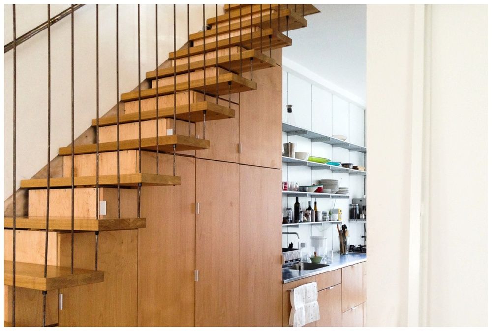 Space under the stairwell doubles as seamless - and clever! - custom cabinetry for kitchen storage!