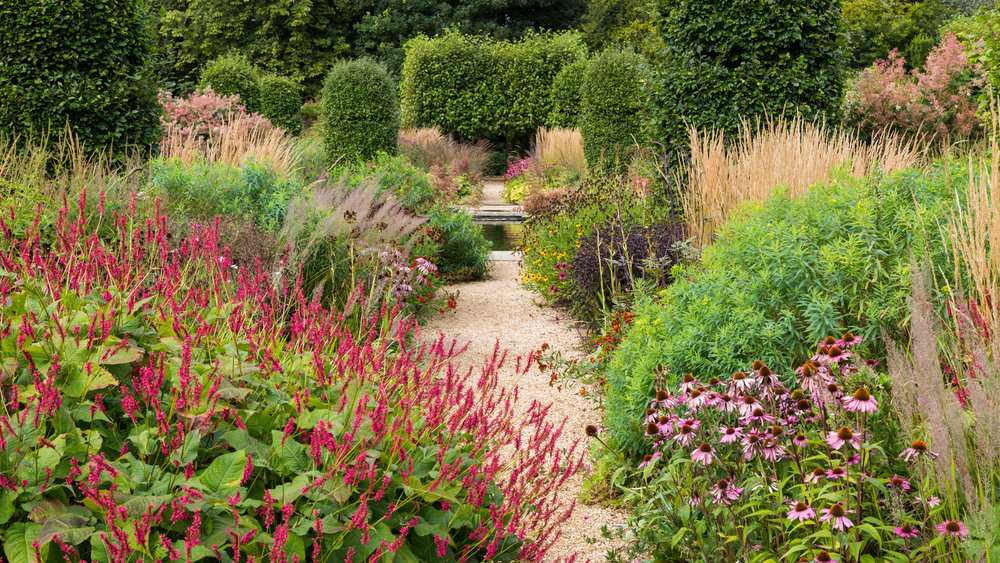Repeated and restrained colour palette of brown, red and pink leads the eye down the path and across the pond on an easy to follow journey. Designer: Tom Stuart-Smith. Image:  Chris Denning/Verve Garden Design.