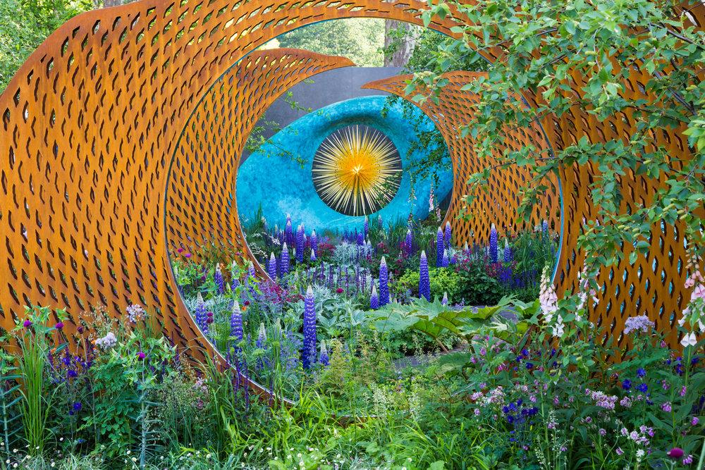 Deep blue lupins, taller than the other plants, lead the eye deep into this garden scene. Designer: Nic Howard. Image: Chris Denning/Verve Garden Design.