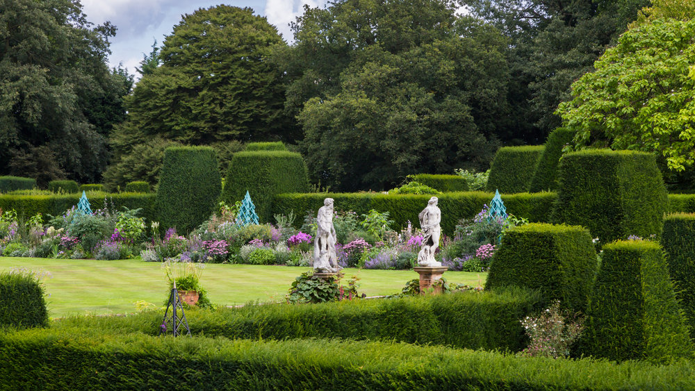 Clipped yew hedges with a random series of topiary create rhythmn and a strong backdrop for the exuberant planting at Renishaw Hall. Herbaceous border designed by Arne Maynard. Image  Chris Denning/Verve Garden Design.