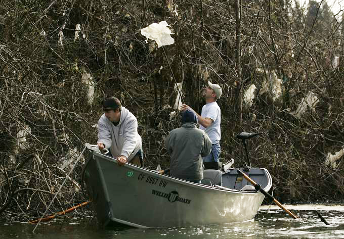 Nick Wheeler of Guerneville, picks off plastic sheeting as he helps to help clean up a dump site on the Russian River just east of Drakes Beach in Guerneville in 2011. (KENT PORTER/ PD FILE)