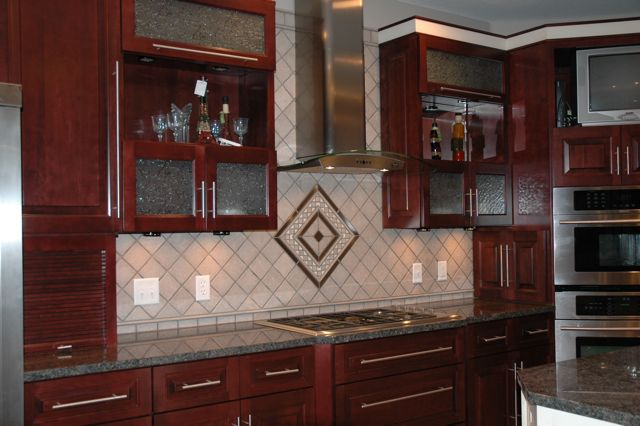 We sandblasted hundreds of 4 inch stone tiles to get exactly the color our customer requested. We custom made the stainless and stone design over the cooktop to coordinate with the stainless steel hood. Classical Glass & Tile also furnished the glass in the cabinet doors.