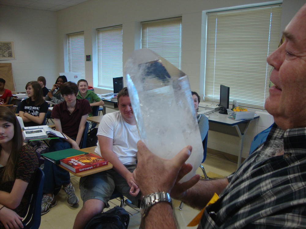 SGS Member Dr. Mike Roberts shows a quartz crystal to a class of freshmen at Caddo Magnet High School.