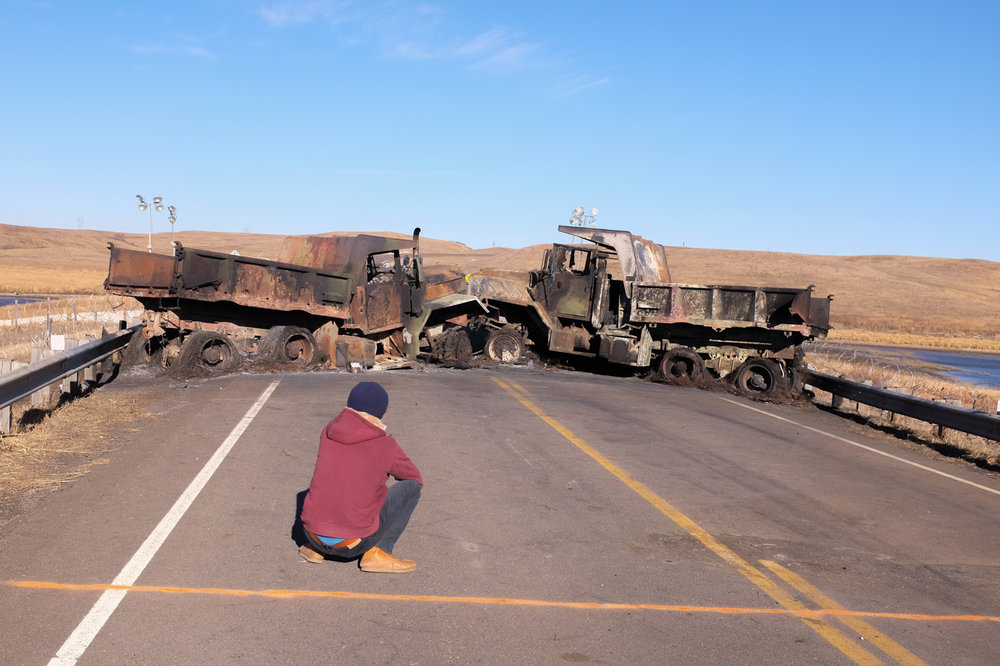 These are the dump trucks blocking state highway 1806 at the bridge over Cantapeda Creek, less than a mile north of the Sacred Stone Camp, less than a mile south of where the pipeline crosses the highway. The battle on November 20 started as water protecters/protesters were trying to clear the  road by pulling the dump trucks out of the way.