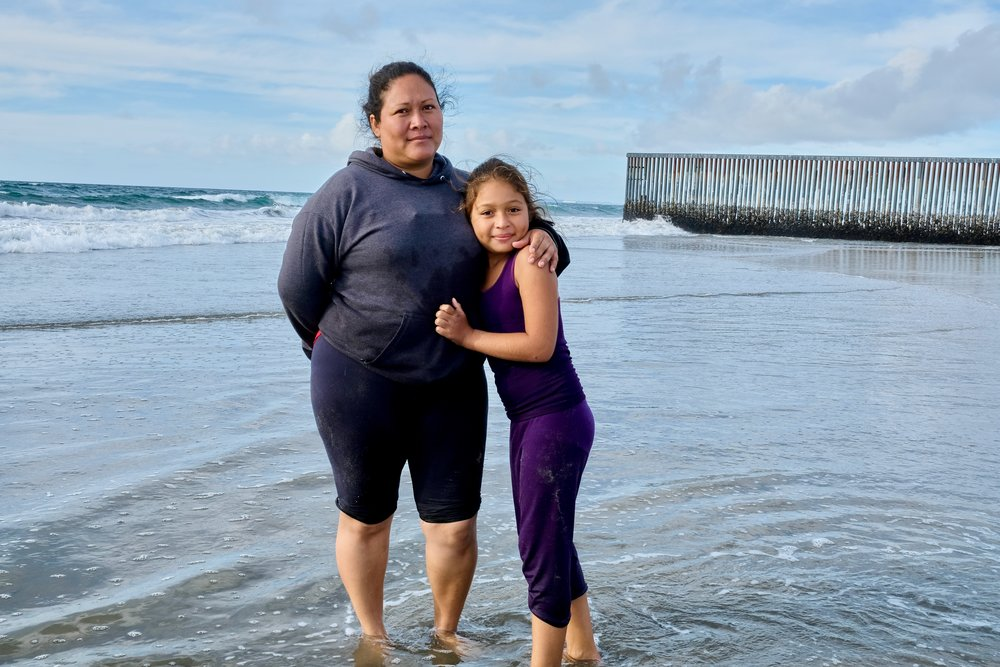 Ruth Pena and her daughter, from El Salvador, at the beach in Tijuana. That's the border wall in the background.