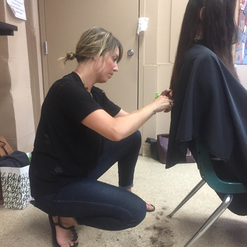 Hotel Arts stylist Kenna getting down and dirty to give her client the perfect cut at last week's Homeless ID fair.